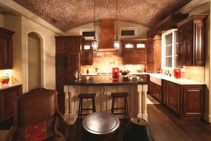 paneled appliances, inside cabinet lighting,apron sink,bar stools,kitchen,two toned cabinets,island