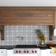 kitchen range hood made from quarter sawn white oak surrounded by white kitchen cabinets