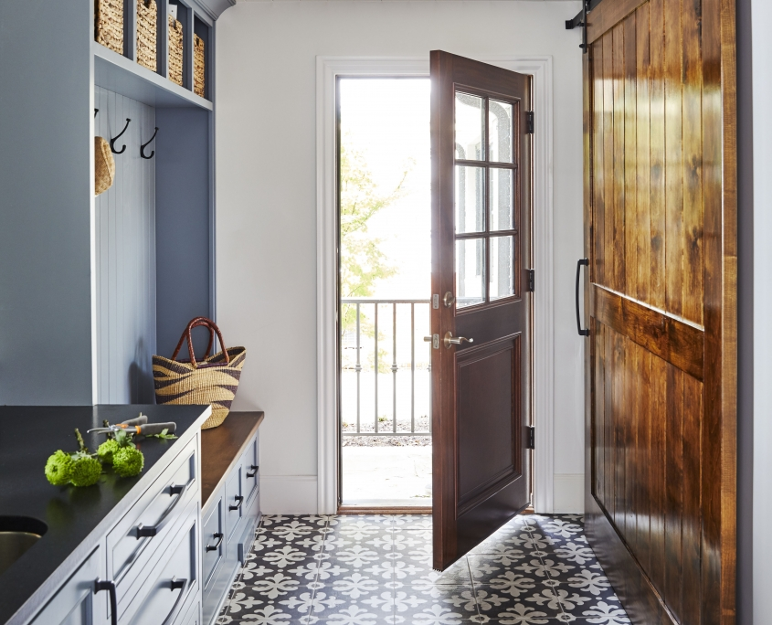 mudroom and laundry room with barn doors and tile flooring, dark countertops and blue cabinets