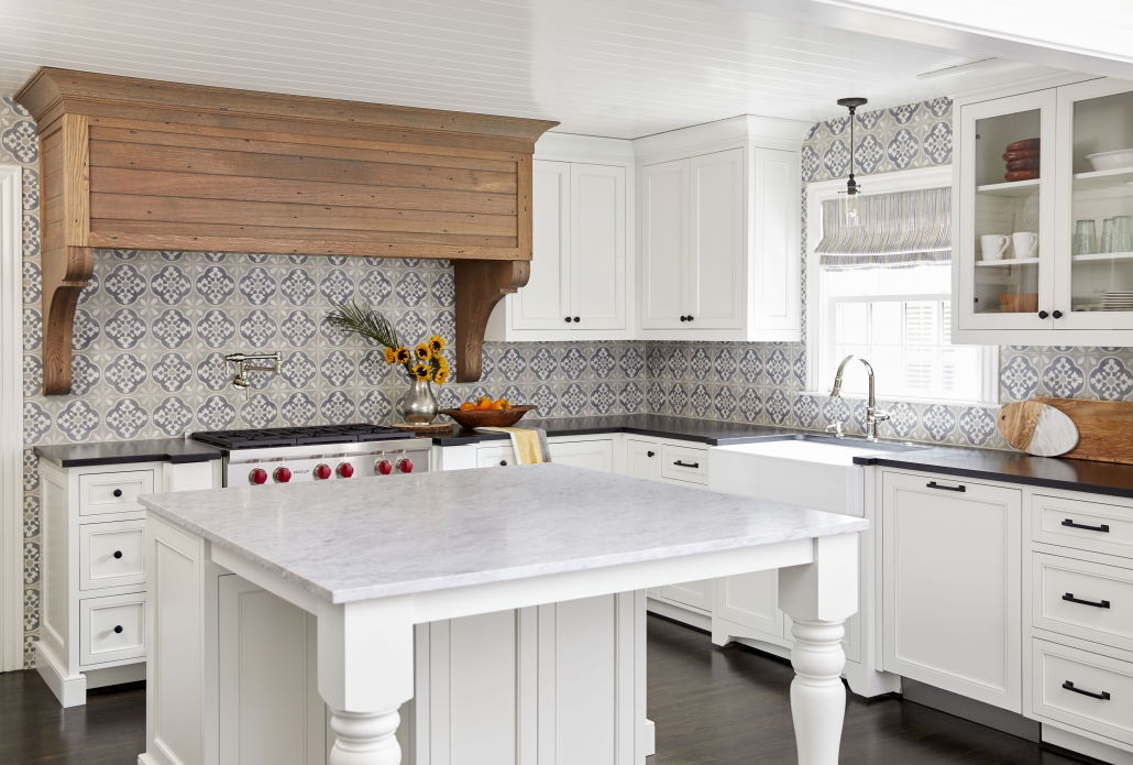white traditional style kitchen with black countertops and custom wood hood